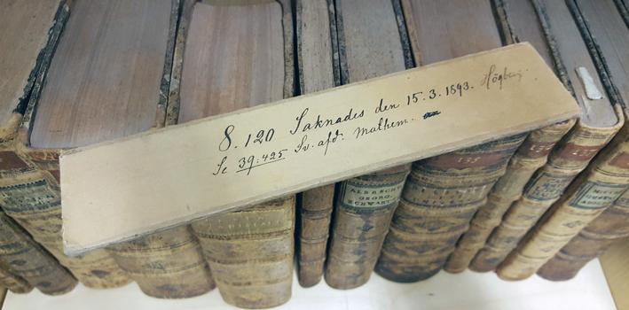 stickan med denna text ligger ovanpå en rad böcker från 1700-talet