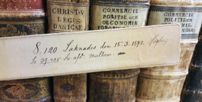 bild på pappsticka med texten som återges i bloggen framför en rad med bokryggar