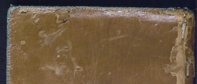närbild på blågrön sydd kant i garn på ett bokband i brunt skinn