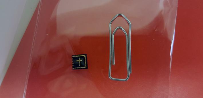 en liten svart bok med ett guldkors på ligger jämte ett gem som är ca fem gånger större i höjd