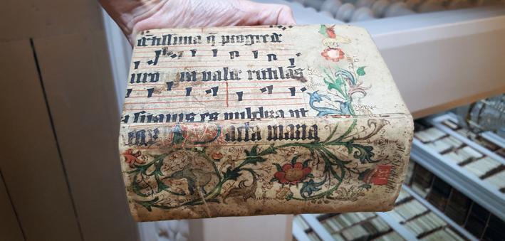 bokens rygg och baksida, målad med blomrankor i glada färger