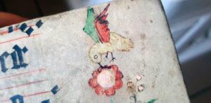 detalj från omslaget med en liten gul fågel på en blomma med en grön och en röd vinge