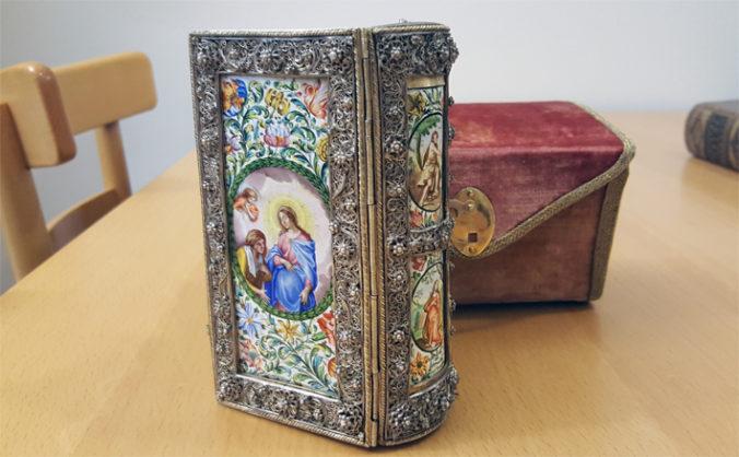 bild på bokband i silver och målat porslin eller fajans, i bakgrunden ett etui till boken klätt i rött sammet
