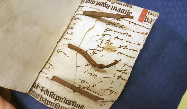 bild på insidan av bakre pärmen med två sorters handskrifter