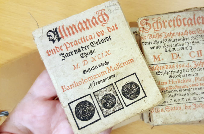 den lilla almanackan ligger i en handflata över en bunt med fler almanackor