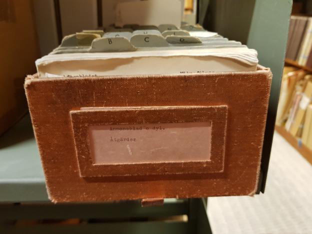 bild på en trälåda med ett kartotek i, och etikett med texter Annonsblad o dyl. Åtgärder på