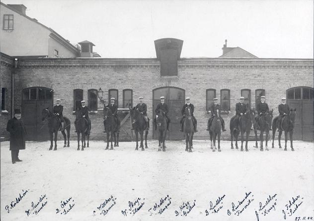 fotografi på en rad ryttare till häst med studentmössor på huvudet