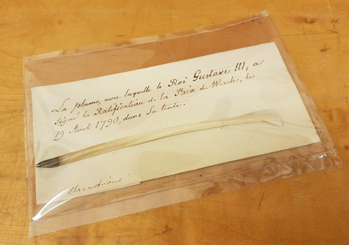 en vit gåsfjäderpenna med bläckdoppad spets ligegr på ett hopvikt brev från 1700-talet i ett omslag av genomskinlig plast
