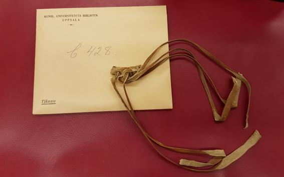ljusbruna läderremmar på ett kuvert som ligger på en röd bakgrund