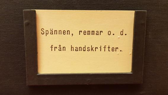 etikett från låda som med texten Spännen, remmar o.d. från handskrifter