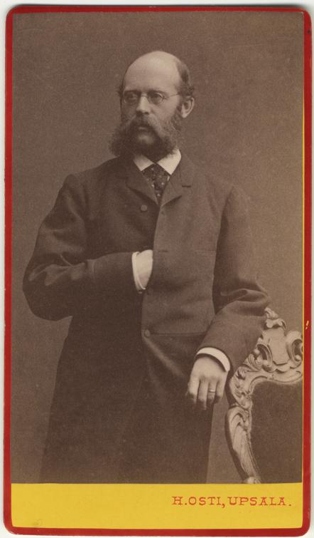 fotografi på en tunnhårig man med skägg och polisonger och glasögon, stående lutande mot en stol med höger hand instucken mot bröstet under kavajen