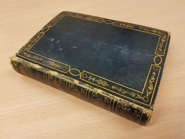 en bok bunden i ett blått skinnband liggande på ett bord