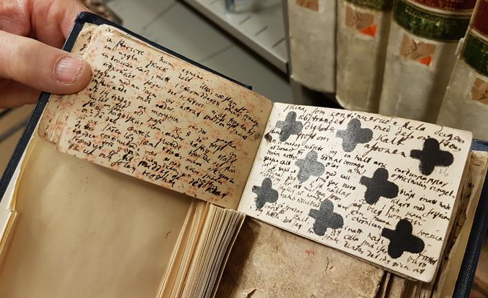 en hand håller upp en bok med inbundna spelkort, fullskrivna med text