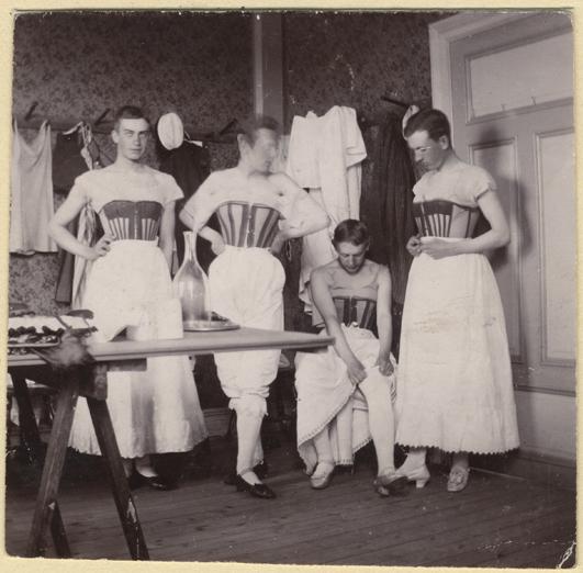 fyra herrar i underkjolar, korsetter och högklackade skor