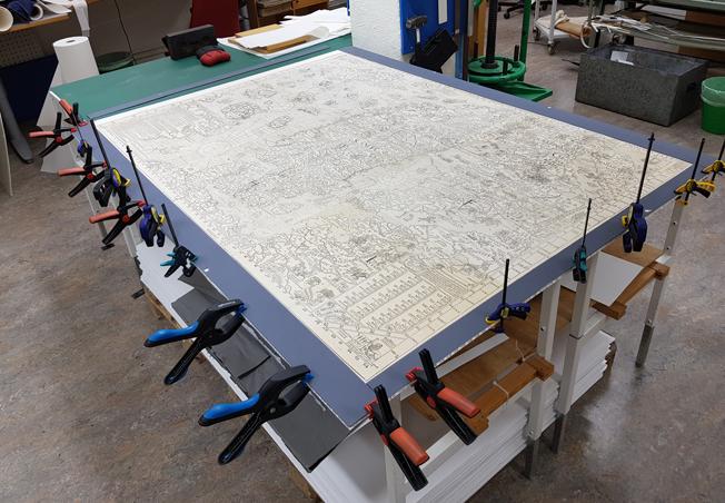 en karta tryckt i svart och vitt över Nordens länder ligger fastklämt på ett arbetsbord med hjälp av en lång rad klämmor i plast mitt i en verkstad full med verktyg och material utmed väggarna