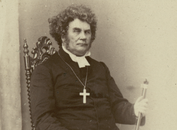 man i prästkrage med stort burrigt hår och bister uppsyn