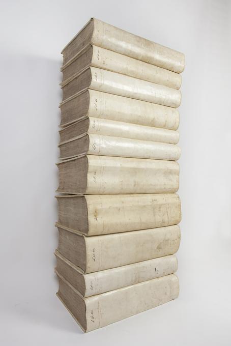 en trave med elva stora böcker bundna i vitt pergament