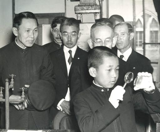 unge Akihito tittar på ett föremål igenom ett förstoringsglas i förgrunden, bakom honom står hans far kejsar Hirohito i kostym och slips, omgiven av en asiatisk tolk och upppklädda europeiska män