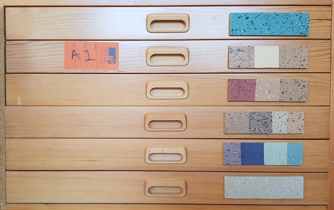 sex byrålådor, varje försedd med färgglad etikett med prov på bokpapper