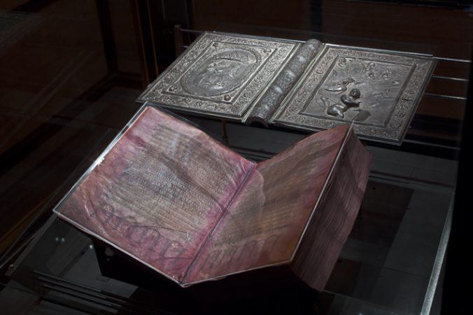 Röda pergamentblad med text i guld och silver, i bakgrunden silverpärmar
