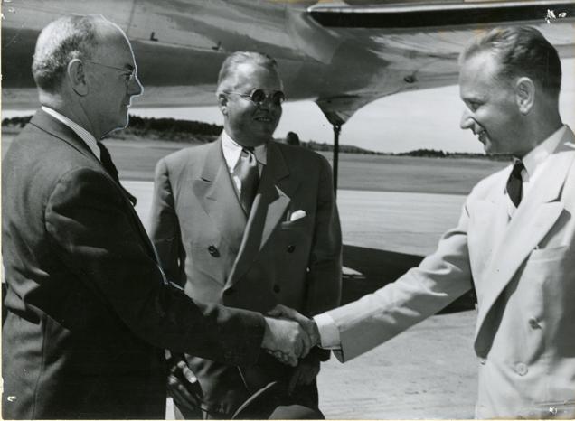 två män skakar hand framför ett flygplan, mannen i ljus kostym till höger är dag hammarskjöld, i bakgrunden står ytterligre ne man i mellanljus kostym och solglasögon. alla ser glada ut.