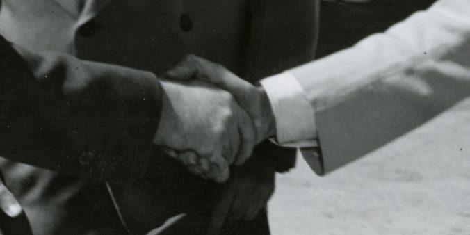 två händer skakar hand, en i ljus och en i mörk kostym