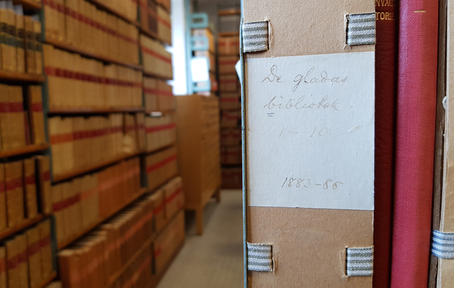 i bakgrunden fulla bokhyllor, i förgrunden en kapsel med texten De gladas bibliotek