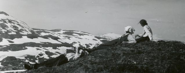 tre personer vilar på branten av ett berg med utsikt över en snöklädd bergstopp