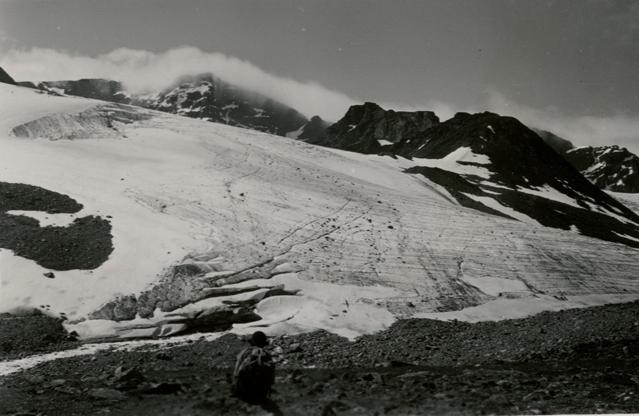 en glaciär med svarta bergstoppar i bakgrunden