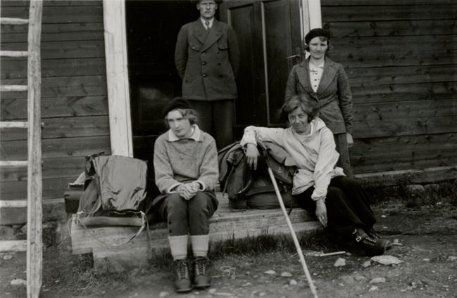 tre kvinnor och en man i vandrarkläder framför en stuga