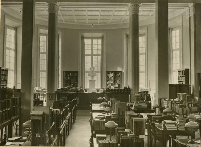 ett fotografi över A-salens bord, med massor av böcker i hyllor ovanpå