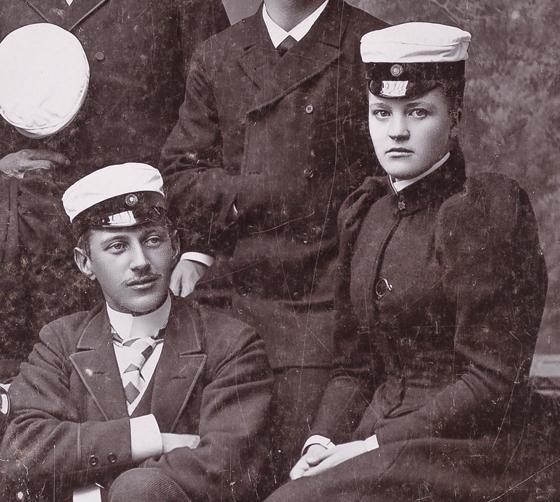 Två sittande studenter, en ung man och en ung kvinna i vita studentmössor och 1800-talskläder