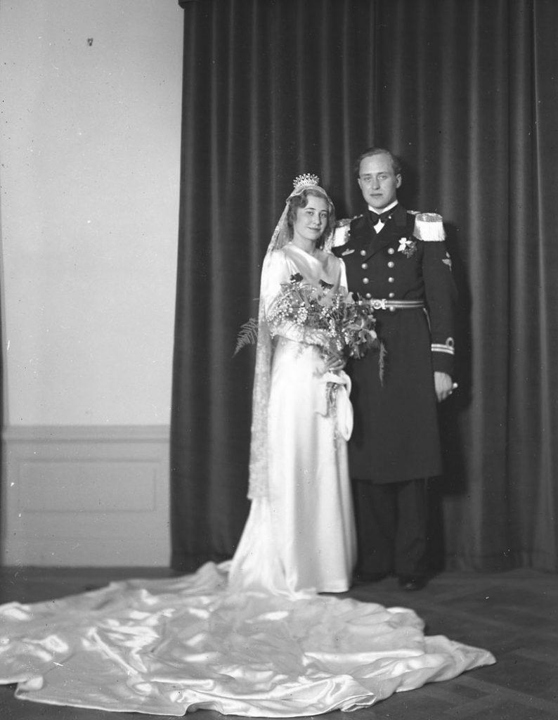 brudparet i helfigur framför en tygridå, hon med krona på huvudet och klänning med ett mycket stort släp draperat på golvet,  och han i uniform med epåletter