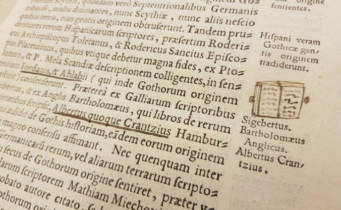 detalj från en boksida, där en bok är tecknad i grönt bläck