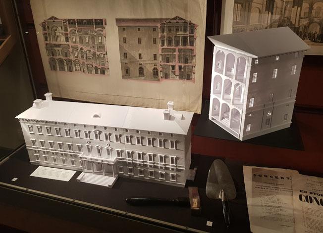 i en monter ligger musrsleven och hammaren bredvid en vit modell i plast av Carolina-byggnaden, i bakgrunden planritnignarna från 1819