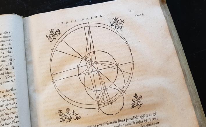 en illustration i form av cirklar som beskriver något astronomiskt, med en tryckt blomma i de fyra hörnen