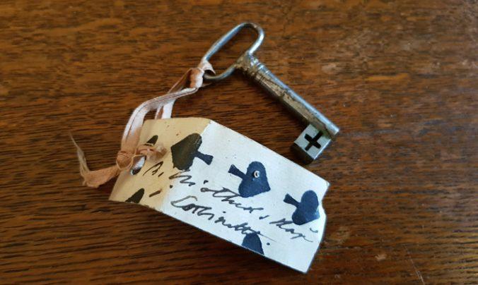 en nyckel på ett träbord, med ett halvt spelkort fastknutet, troligen spader tio