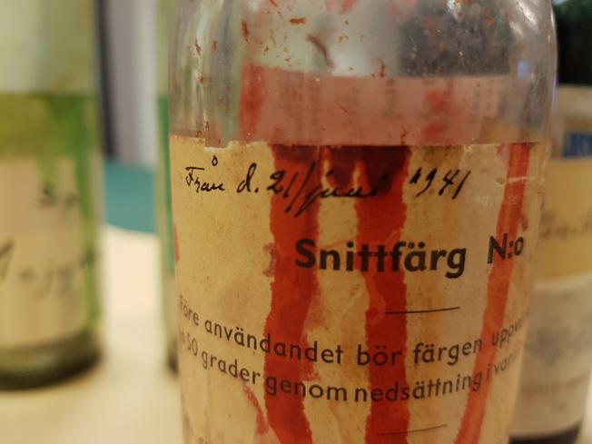 närbild på en glasflaska där det runnit röd färg över pappersetiketten som lyder: snittfärg.