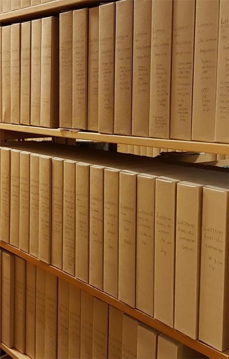 rader med bruna kapslar i ett bibliotksmagasin, på ryggarna står Sv. Lotterier