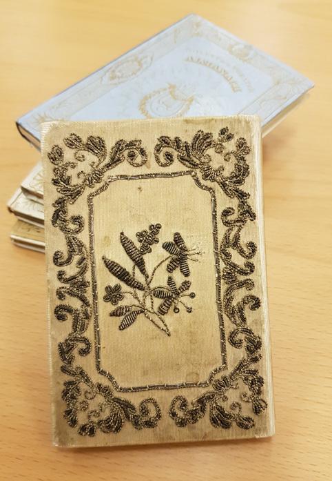 baksidan av bokbandet med broderade blommor i guldbroderad ram, i bakgrunden fler almanackor med pappärmar