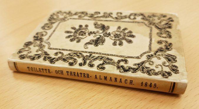 En liten beige bok med guldbroderier på ligger med ryggen mot betraktaren, på ryggen en tryckt titel