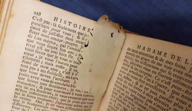 en liten papperslapp med spår av bläck mellan bladen i en bok
