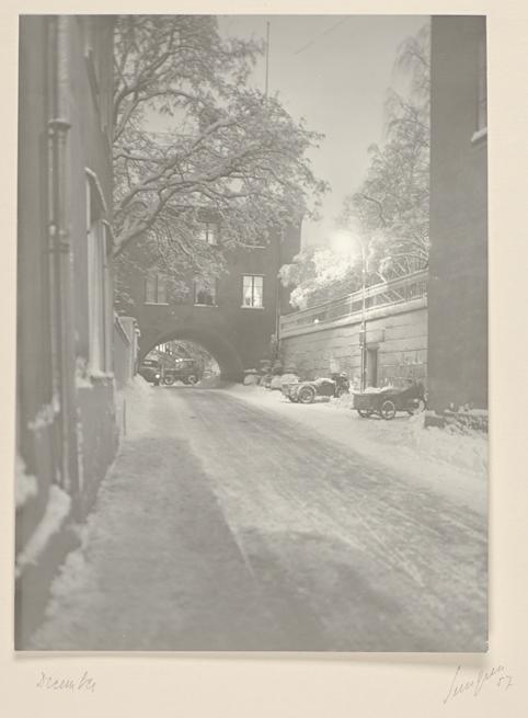 en snöig väg, i bakgrunden valvet under skytteanum, till höger två översnöade flakmopeder och genom valvet en traktor