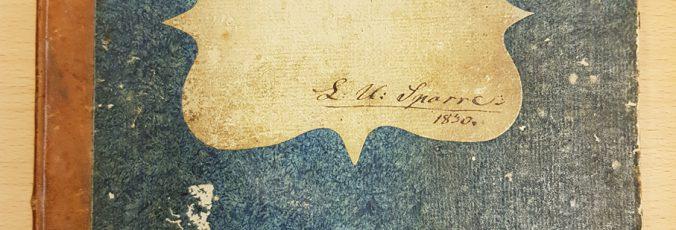 detalj från bokens blå omslag, med etikett med namnaet L. U. Sparre och årtalet 1830