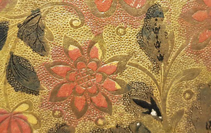 detalj från brokadpappret, en röd blomma mot grön bakgrund, med kantlinjer och pounkter i bakgrunden i guld