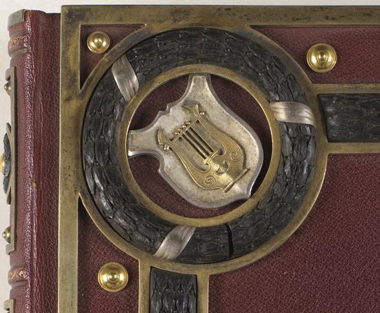 detalj från albumets pärm med en lyra i silver på