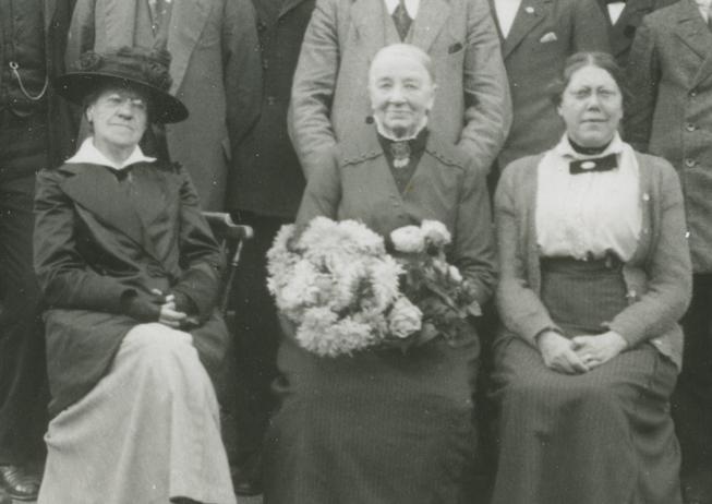 tre sittande äldre kvinnor, den mittersta med en stor blombukett i knät