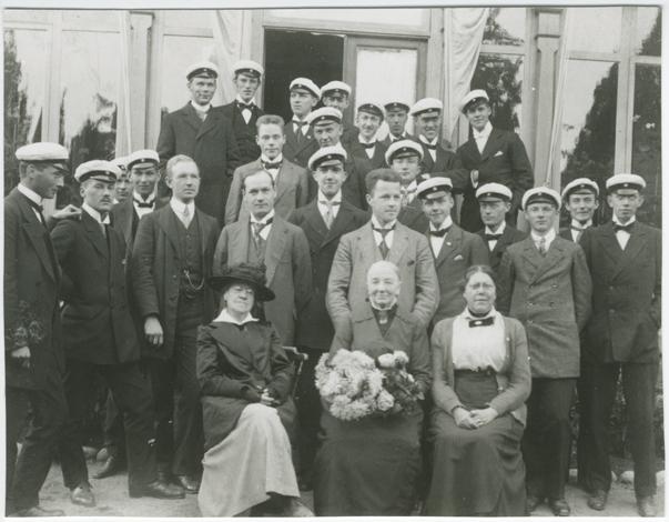 En mängd unga män med studentmössor stående bakom tre äldre sittande kvinnor