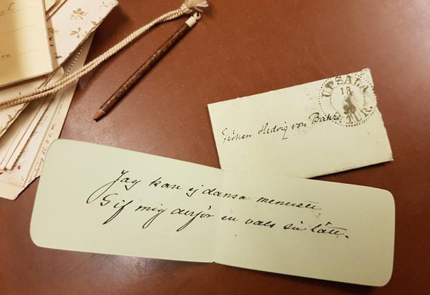 en liten vikt papperslapp vid ett litet kuvert, stämplat av posten