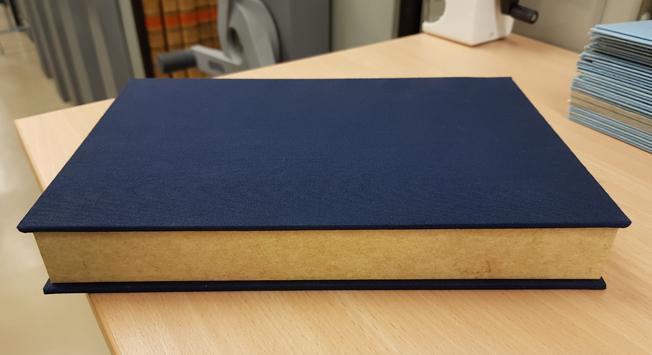 En kornblå kapsel klädd i blått tyg med en kant av gult papper